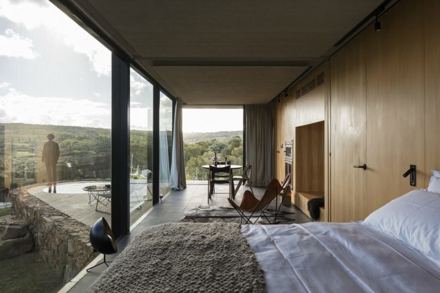 The bed is enclosed by glass walls, allowing visitors to see the mountains that surround each cabin.