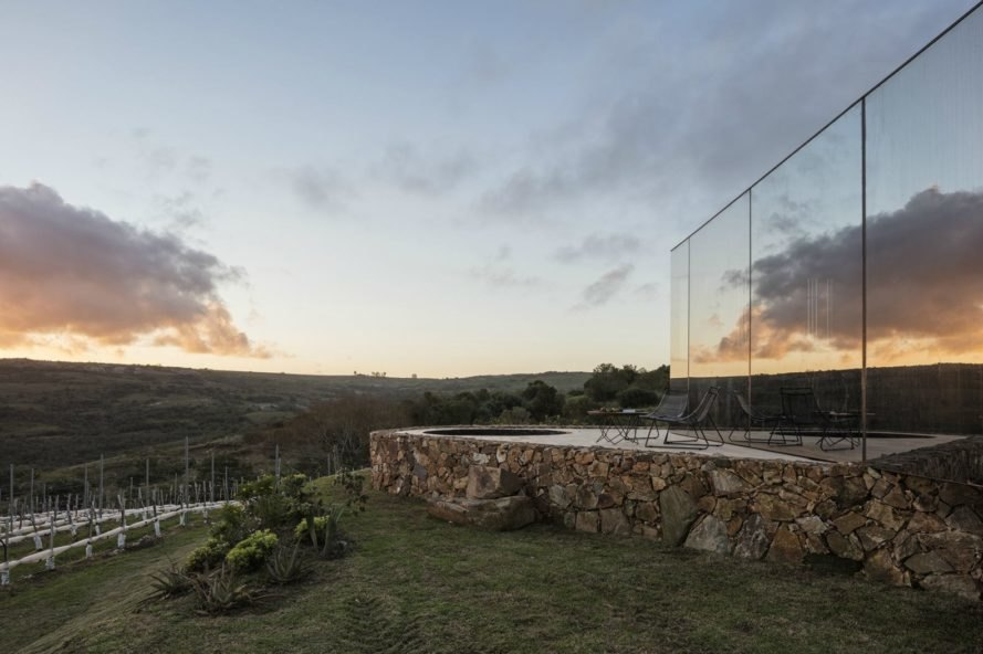 The mirrored facade reflects the sky. The pool and patio area looks out onto the mountainous landscape.