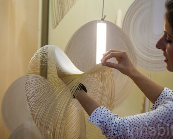 Woman touches the OLED panel inside the Sila lamp.