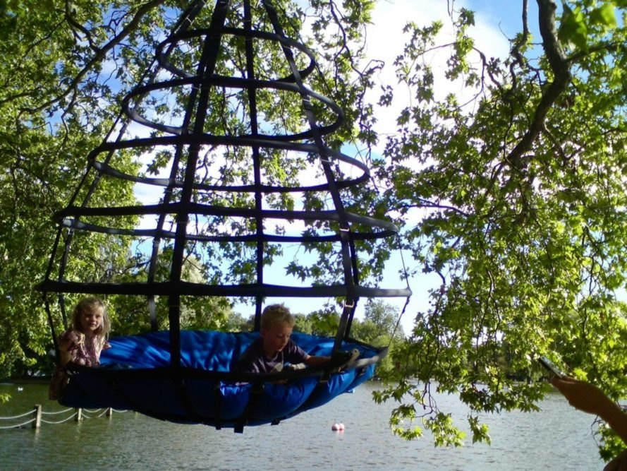 Two kids swinging in the Sky-Pod Hanging Tent