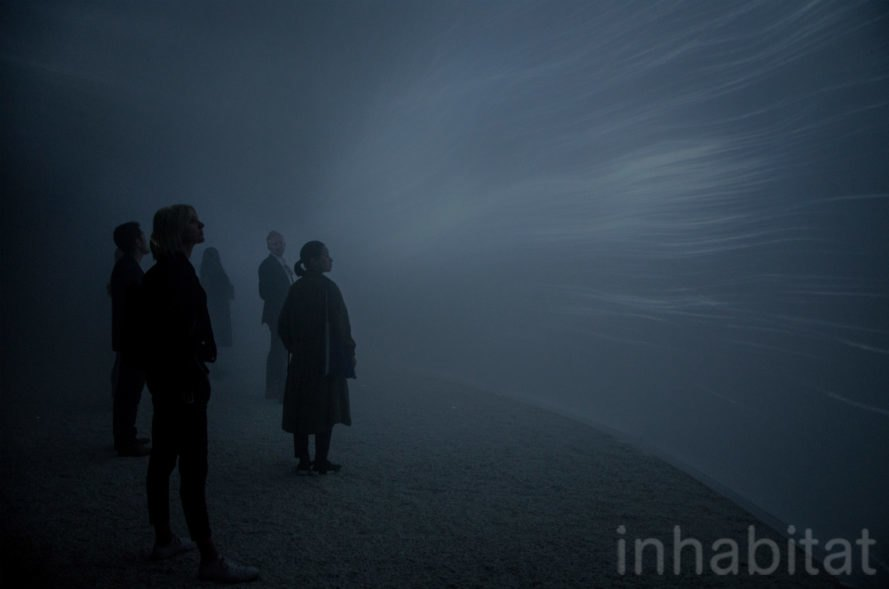 People stand inside the misty dome.