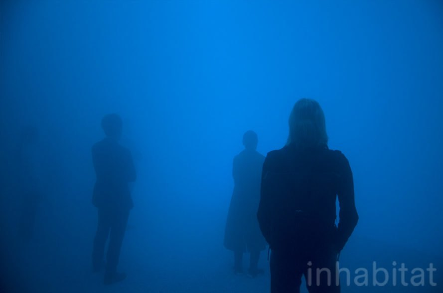 People stand in the blue light of the mist-filled dome.