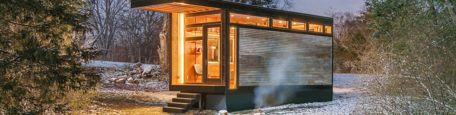 The Cornelia Tiny Home is surrounded by forest. Just outside of the home, a fire burns in a pit.