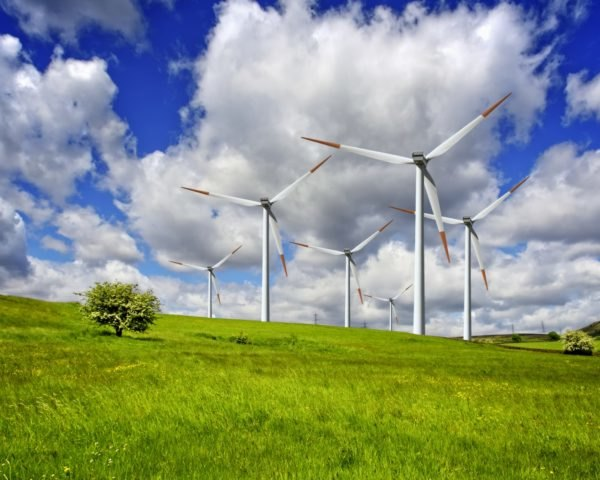 Wind turbines are on rolling green hills.
