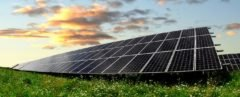 An array of solar panels on a grassy field at sunset