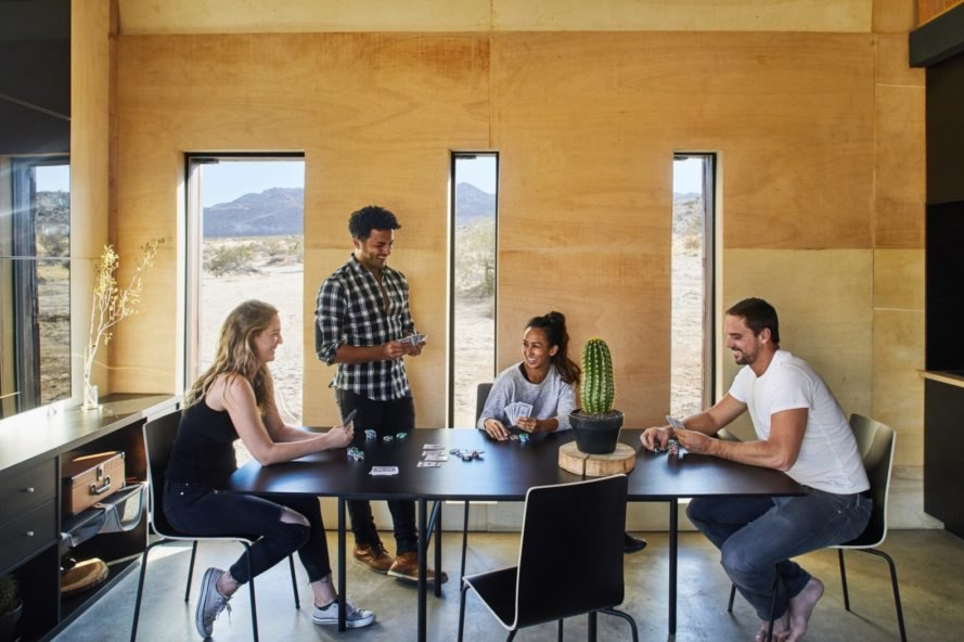 four people sitting at a table inside a wooden cabin