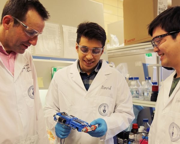 University of Toronto researchers hold their portable 3D skin printer