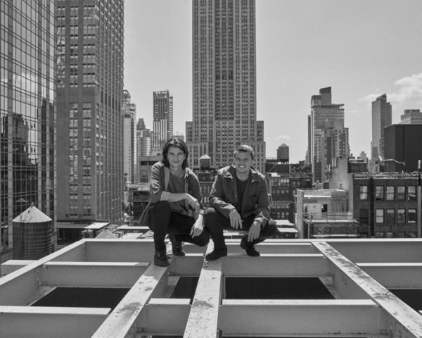 Bjarke Ingels and Adam Neumann in New York City on the frame of a building.