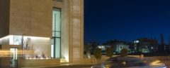 A bank at night with an illuminated facade and stairway