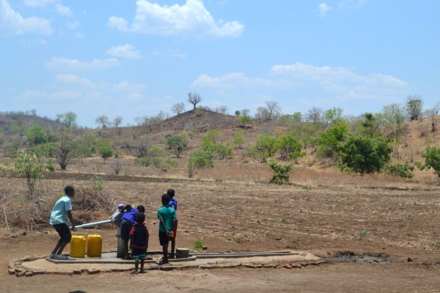 Children in Malawi obtain water from a water pump in a drought-impacted region