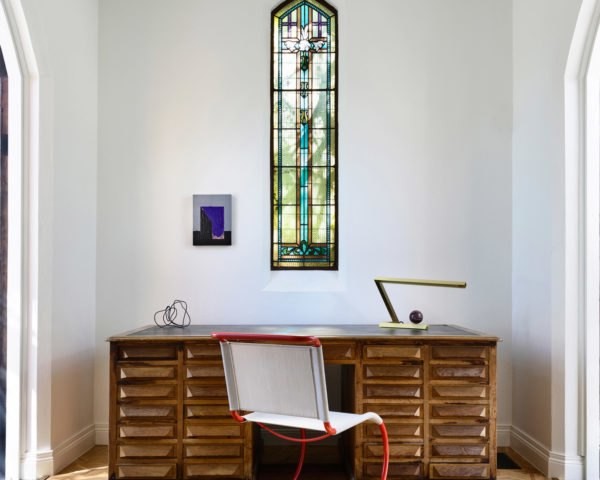 A modern desk and chair underneath a stained glass window.