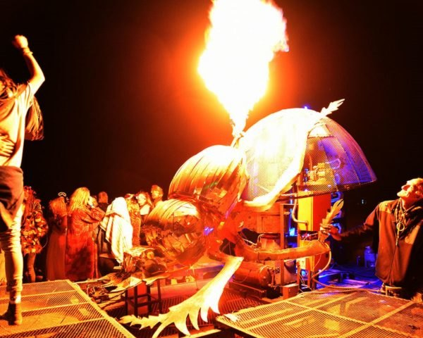 A metal dung beetle shooting flames into the air at night