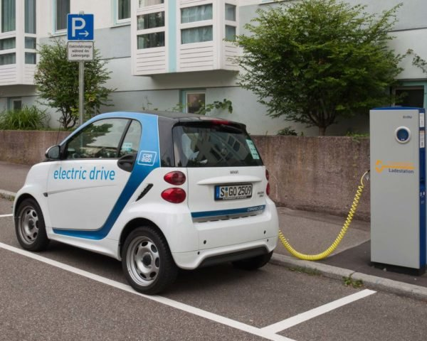 An electric smartcar charging at a curbside power station