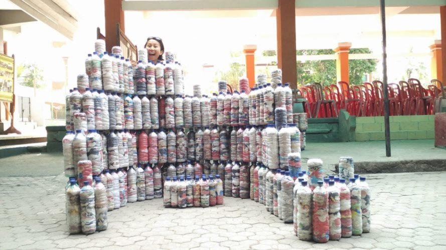A person stands behind stacked ecobricks