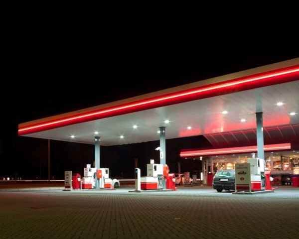 A gas station lit up with red neon at night