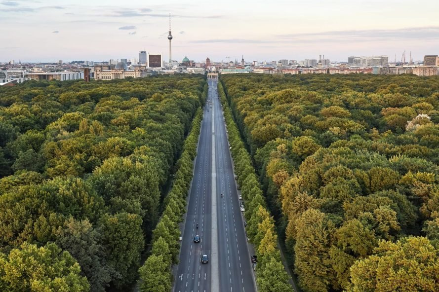 Highway between trees leading into the city of Berlin