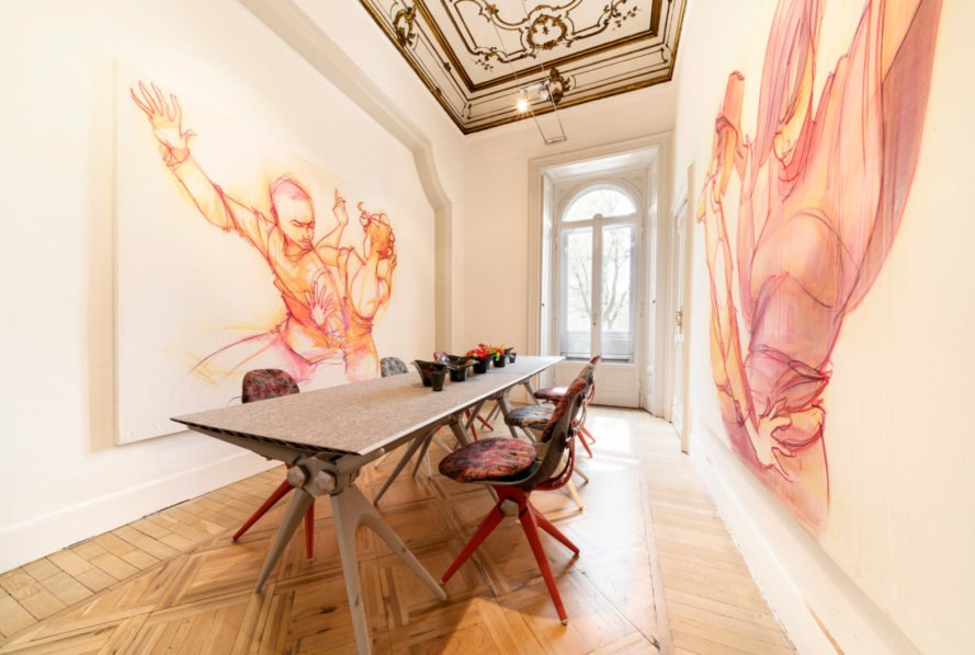 an interior room with a long table and artwork on the walls