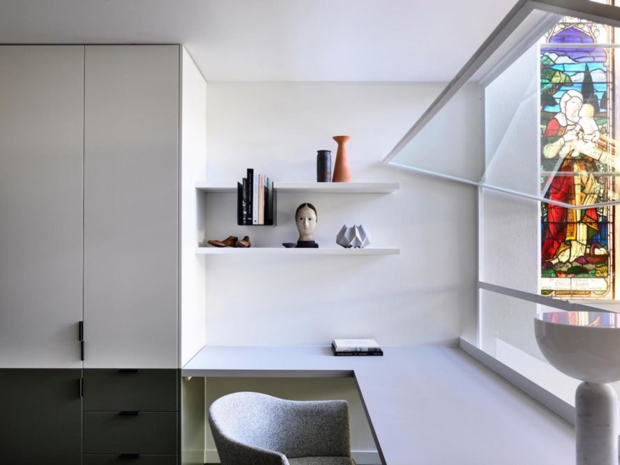 A modern office space with white paneling and a stained glass window.