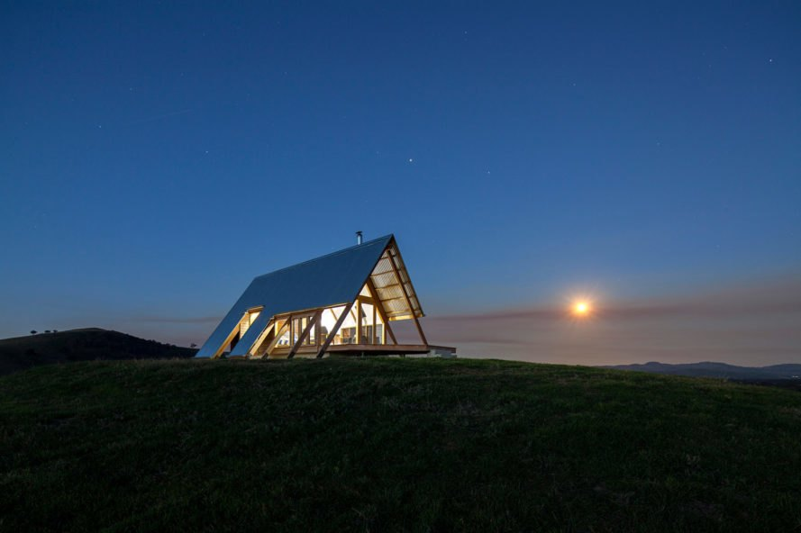 night shot of timber and glass cabin