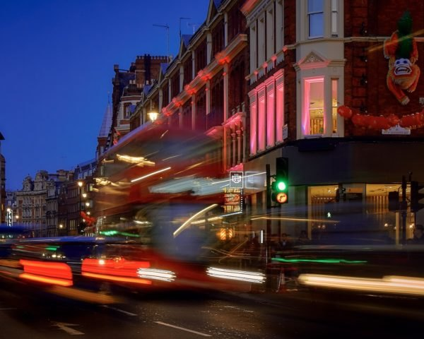Buses and cars zoom along a busy street in London
