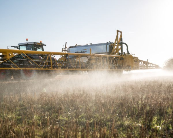 Farm machine spraying field with glyphosate