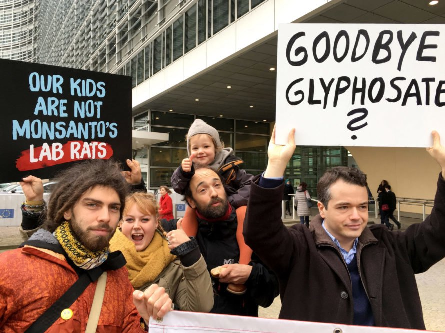 "Group of people hold signs reading ""Our Kids are not Monsanto's Lab Rats"" and ""Goodbye Glyphosate"""