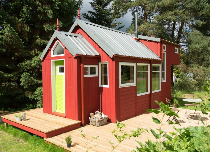 red tiny home with wooden deck