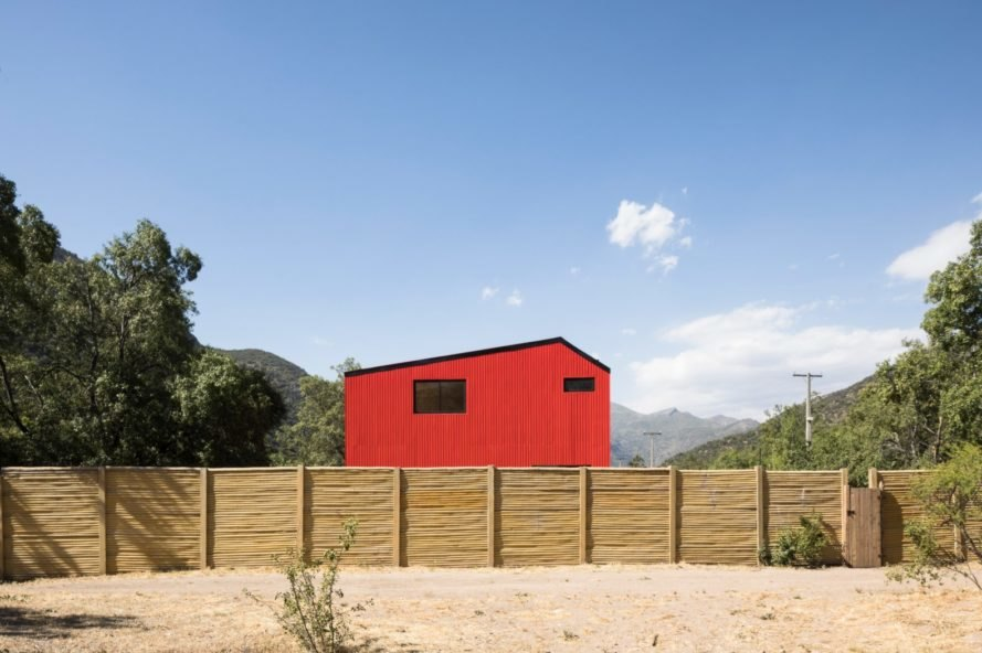 large red home surrounded by wooden fence