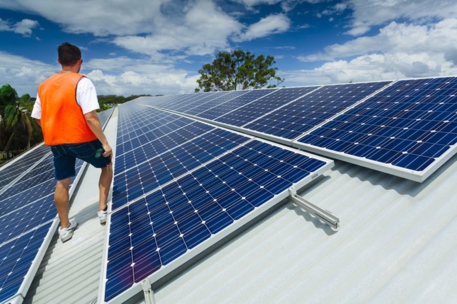 A technician inspects solar panels atop a factory roof