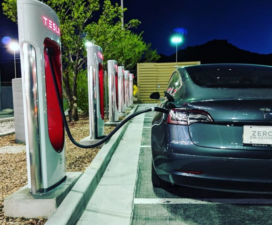 Tesla electric car charging at a station