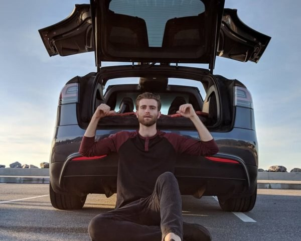 Nico Nevolo sitting in front of the open trunk of his Tesla Model X