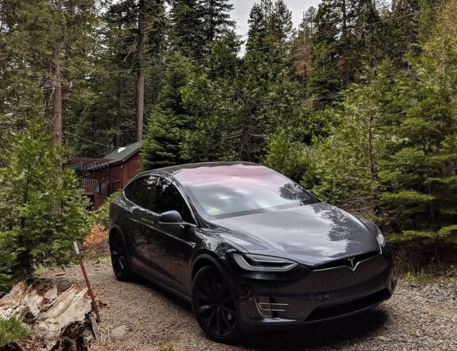 Tesla amidst the trees, near a cabin in Tahoe