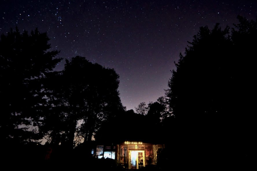 a night shot of a home with trees in the background