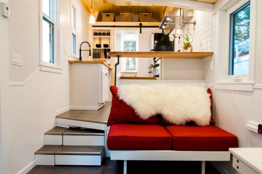 red sofa and stairs leading into a kitchen