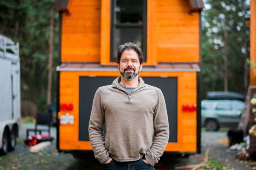 man standing in front of a tiny home