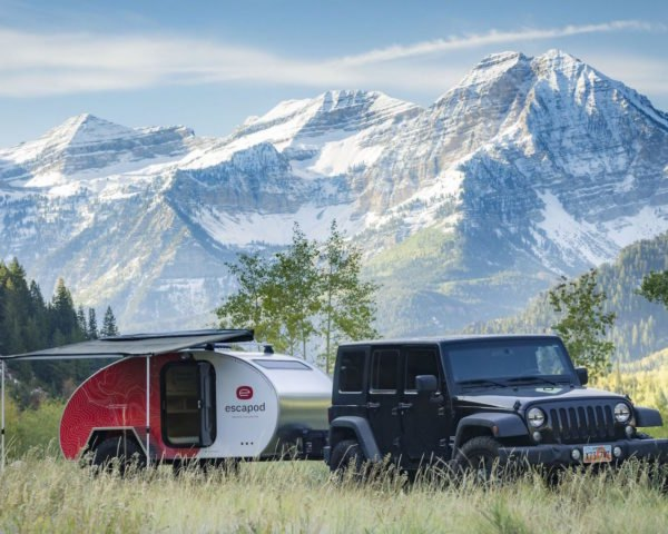 A jeep with a teardrop trailer attached against a backdrop of mountains.