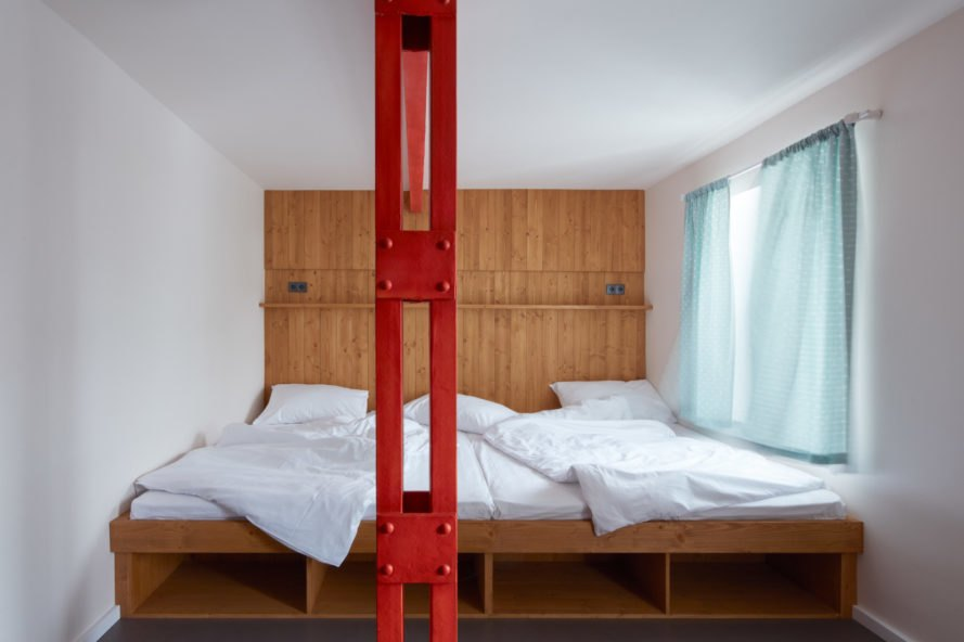 bed with wooden platform and red pillar