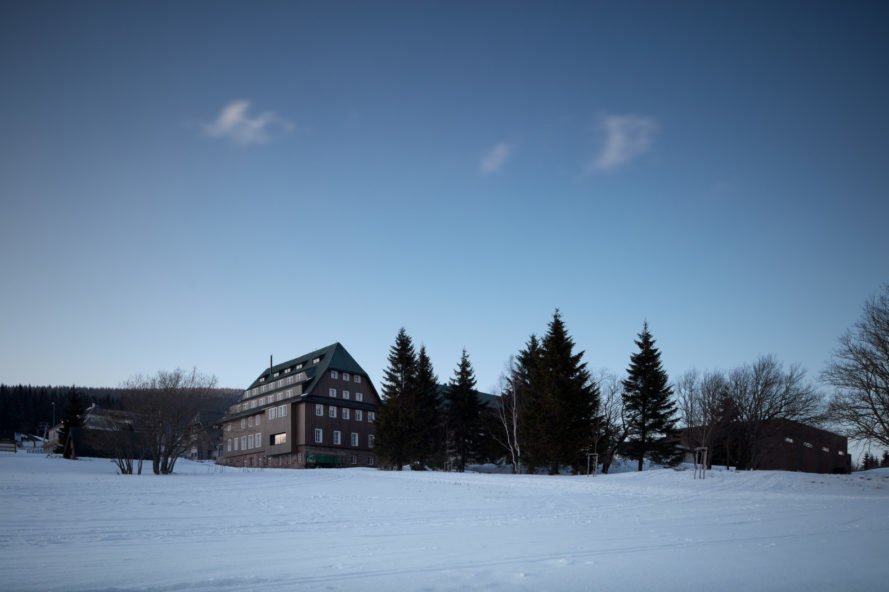 snowy landscape with building and trees in the background