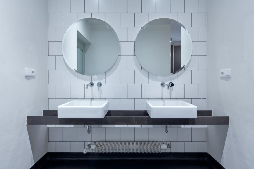 bathroom with subway tiles and two mirrors and sinks