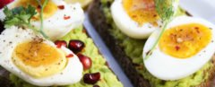 Close-up of avocado toast with hard-boiled eggs and pomegranate seeds