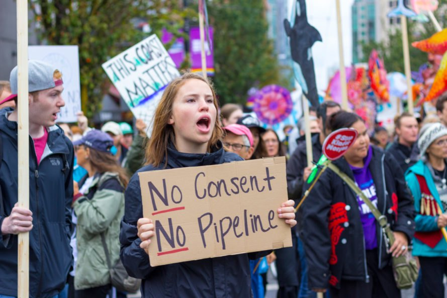 "Woman holds sign that says ""No Consent, No Pipeline"""