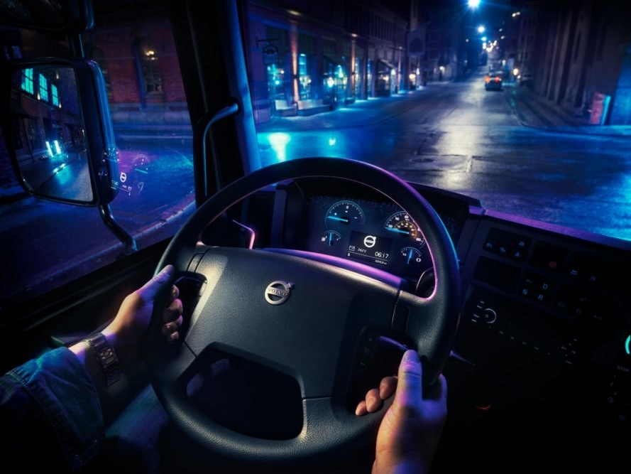 The steering wheel and driver's seat view from inside a Volvo electric truck at night
