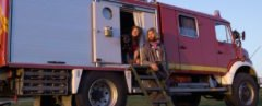 Couple sitting in doorway of old fire truck converted into a camper