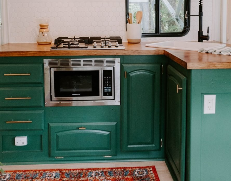 a kitchen with green cupboards