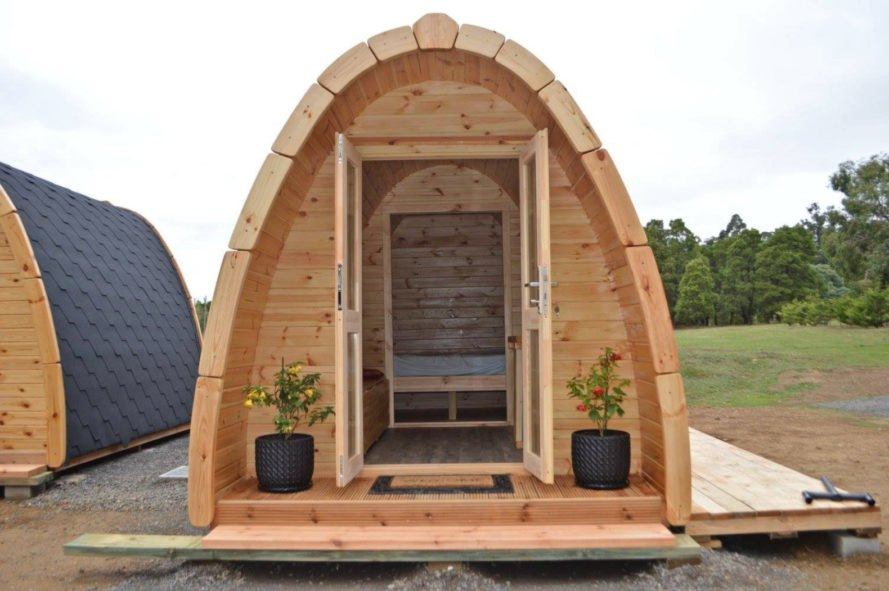 a curved wooden cabin with open doors