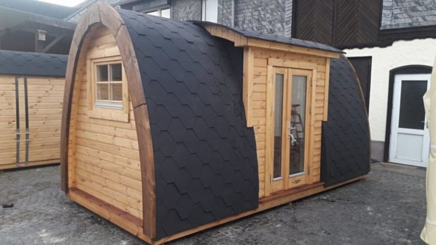 A curved cabin with black shingles