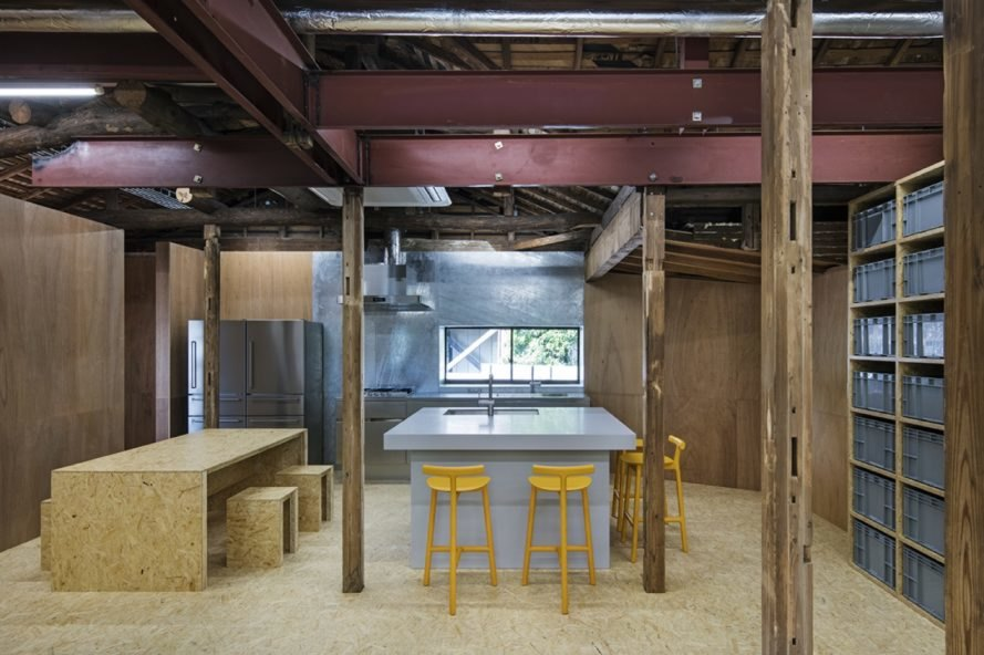 kitchen with stainless steel refrigerators, a large island with yellow stools, and a timber dining table and chairs