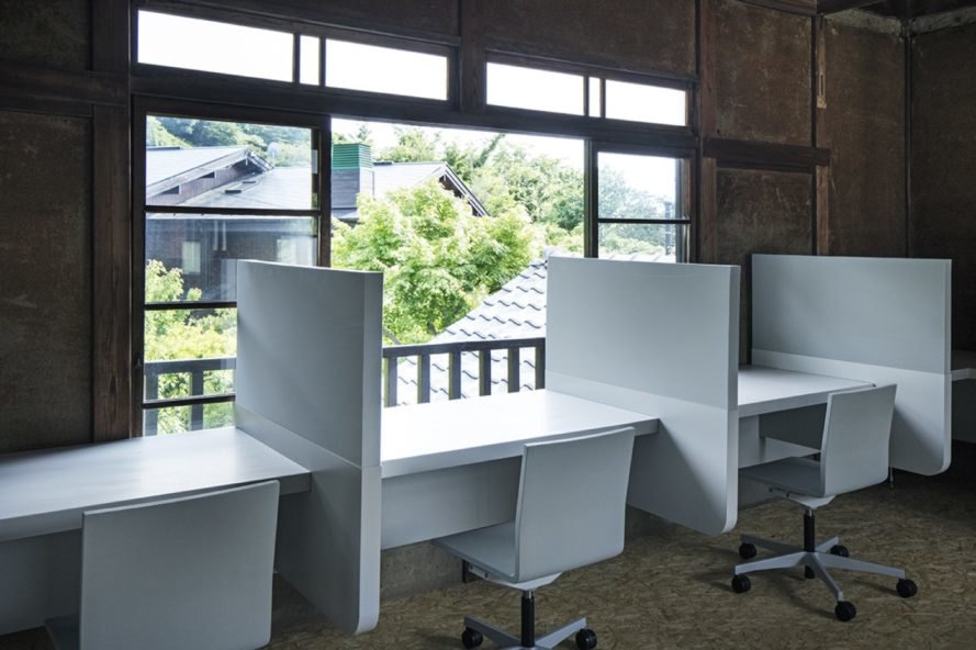 office area with three cubicles facing a large window