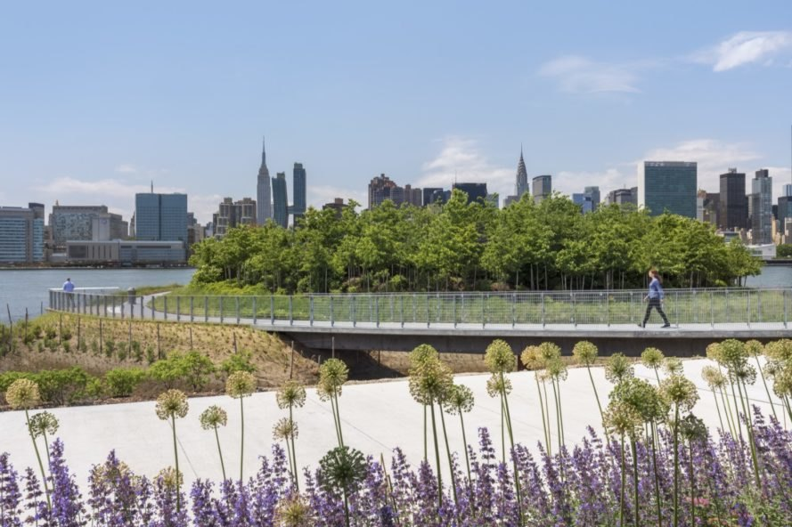 platform filled with greenery that faces Manhattan skyline
