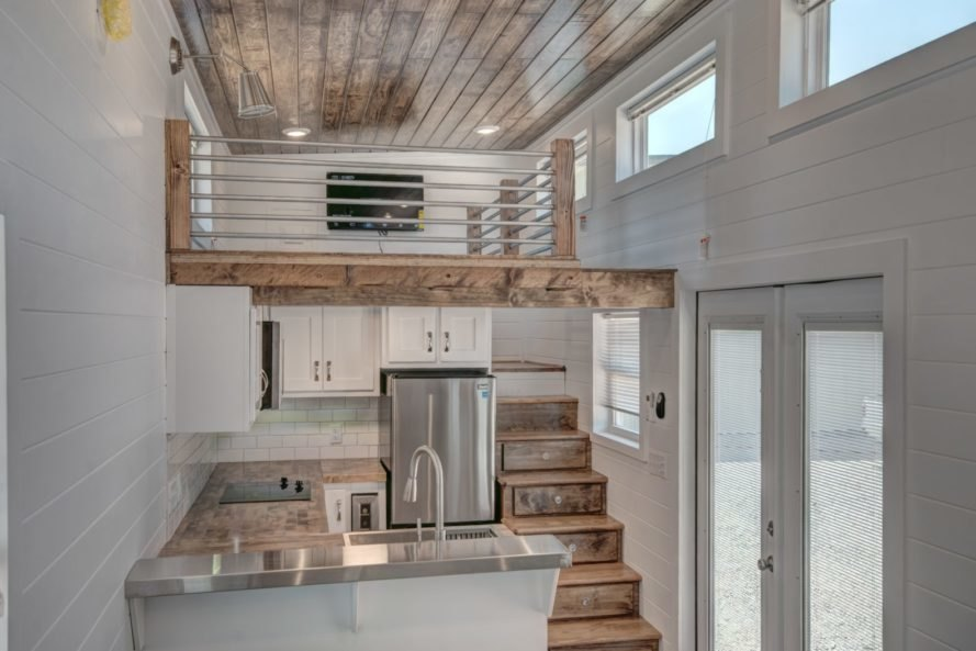 living room with sleeping loft above